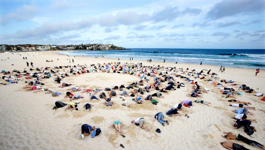 People lying on Bondi beach with their heads in the sand