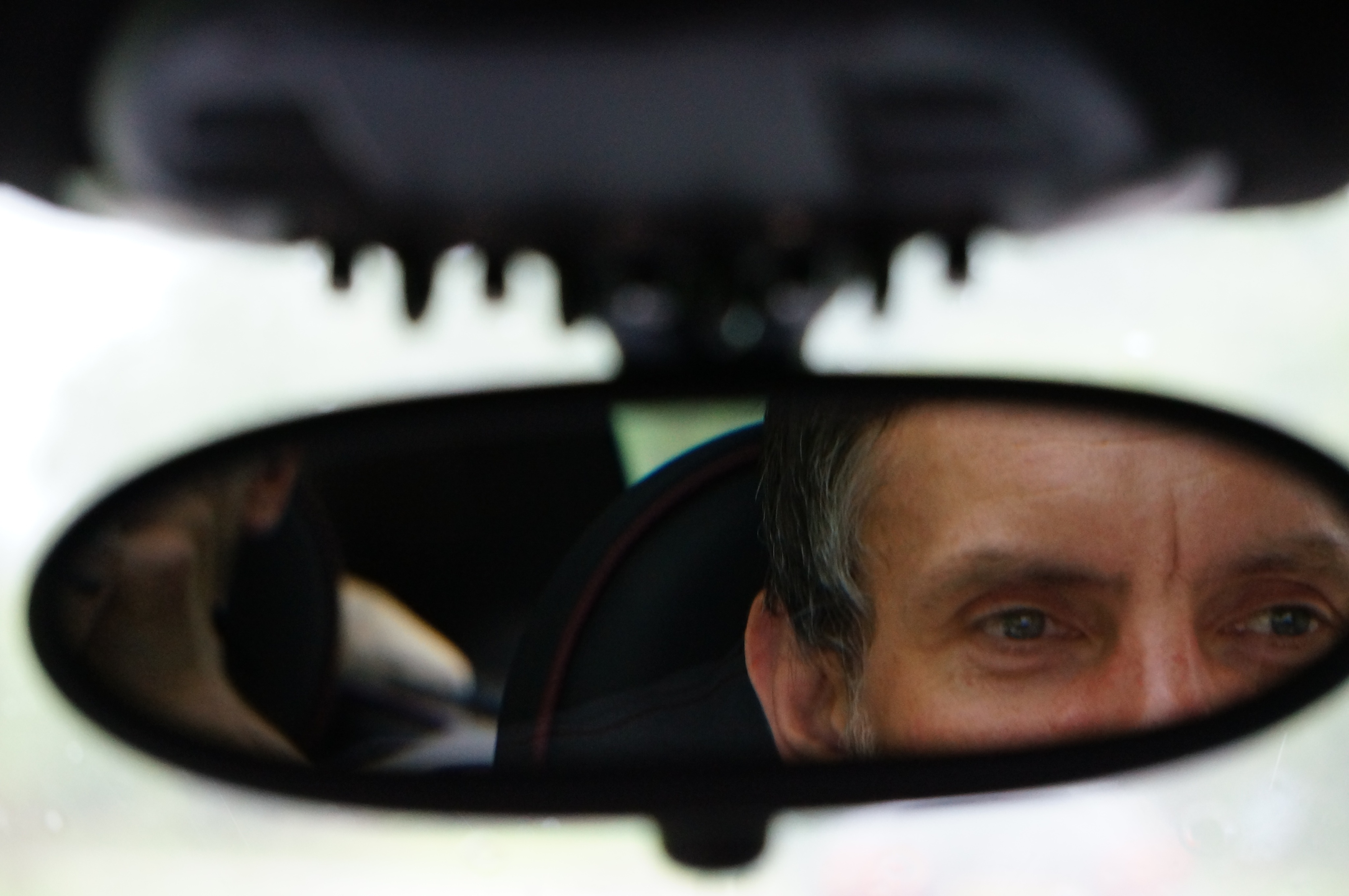 Rear vision mirror showing part of man's face